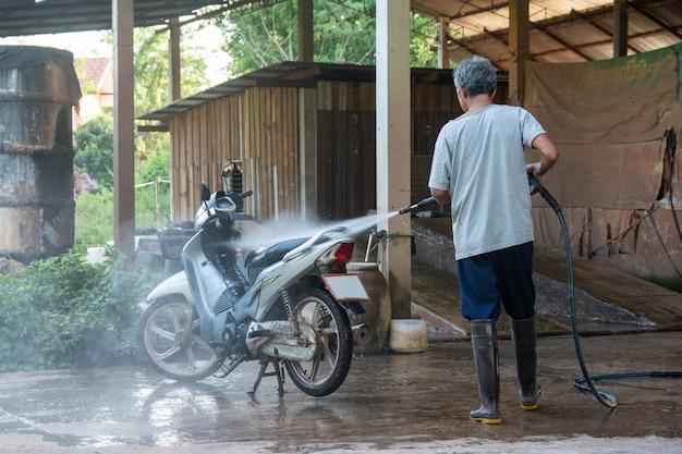 Velho homem lavar sua moto com alta pressão lavadora na loja de lavagem de carro