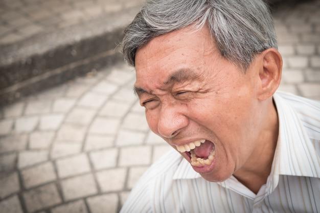 Velho idoso gritando e gritando de dor