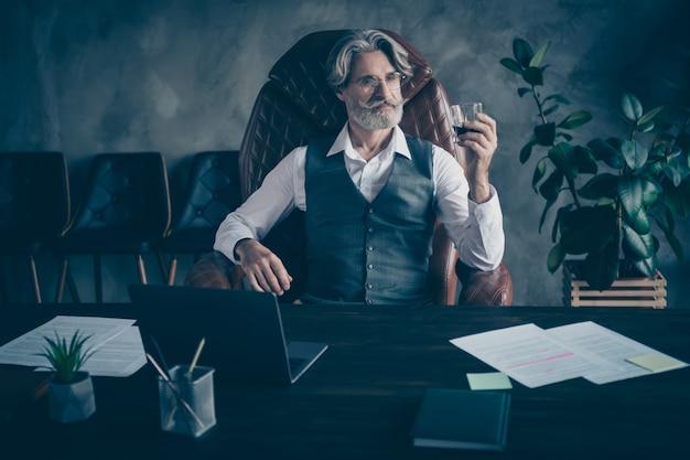 Velho inteligente empresário sentado na mesa bebendo conhaque no escritório