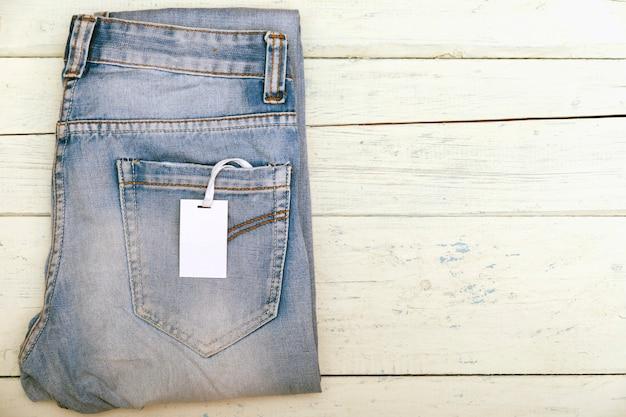 Velho jeans curto na mesa de madeira branca rústica