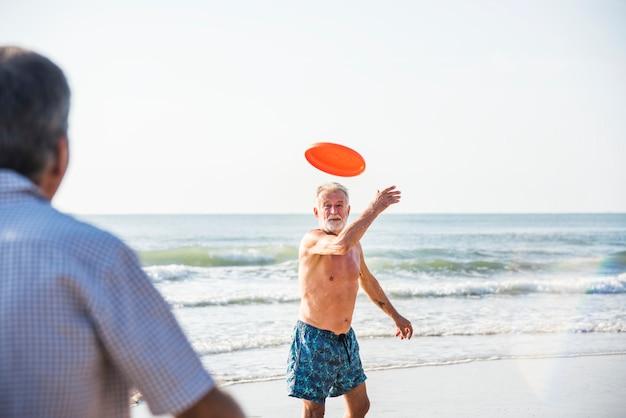Velho jogando um frisbee para seu amigo
