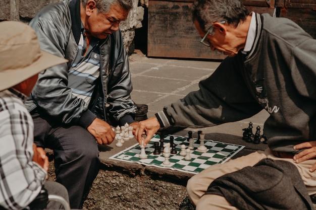 Velho jogando xadrez, inclusive, cadeira de rodas.