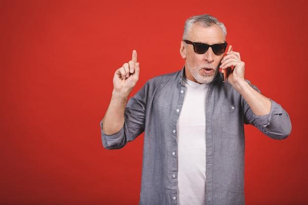 Velho legal sênior em casual falando no telefone celular em elegantes óculos de sol aviador homens elegantes isolados.