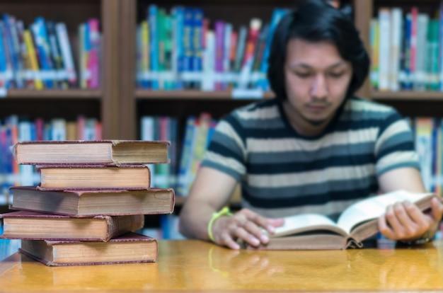 Velho livro sobre a mesa na biblioteca com o homem lendo o livro plano de fundo