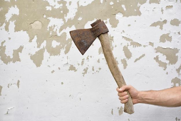 Velho machado enferrujado na mão do homem contra a parede gasto.