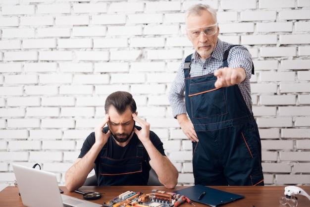 Velho mestre de computador irritado ensina homem estressado.