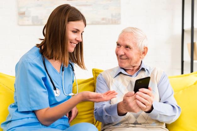Velho mostrando fotos no telefone para cuidador