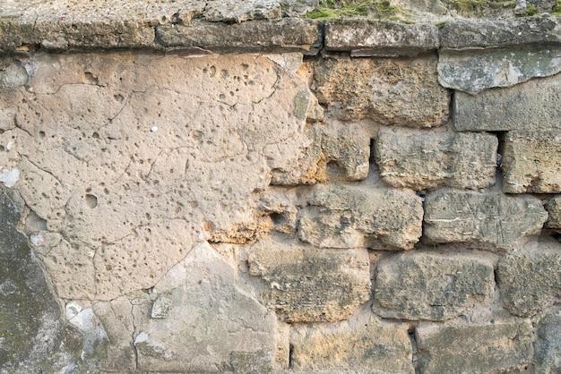 Velho muro de pedra rachada com riscos de pedras visíveis