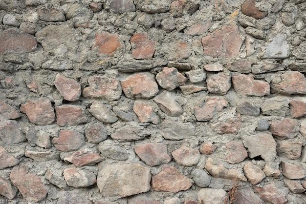 Velho muro inacabado de pedras de várias formas e cimento.