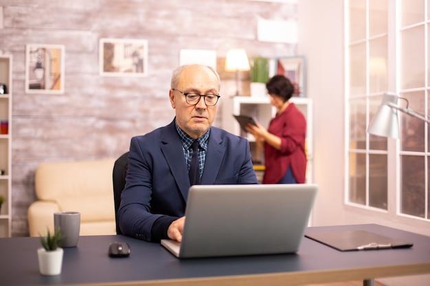 Velho na casa dos 60 anos trabalhando em um laptop em uma aconchegante sala de estar enquanto sua esposa está no fundo