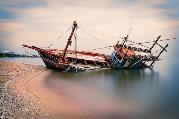 Velho naufrágio na praia durante o pôr do sol em pattaya, tailândia
