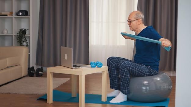 Velho no treinamento de bola de equilíbrio com banda de resistência, assistindo ao programa de fitness online. idoso reformado treino saudável saúde desporto em casa, exercício de actividade física na velhice