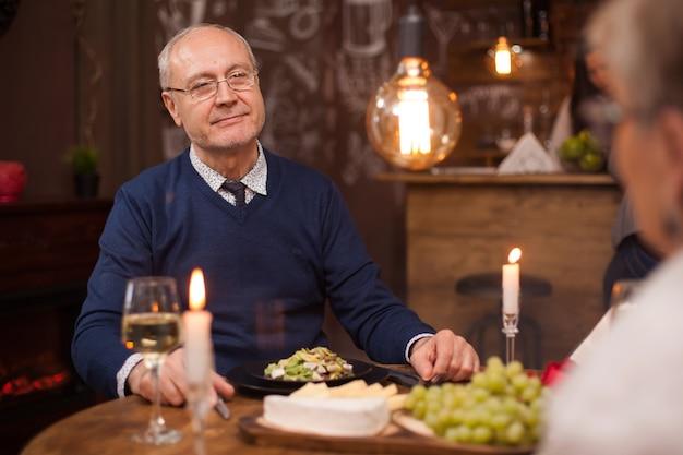 Velho olhando com admiração para sua velha depois de todos esses anos de casamento. casal velho romântico. lindo casal de velhos em um restaurante. copo de vinho.