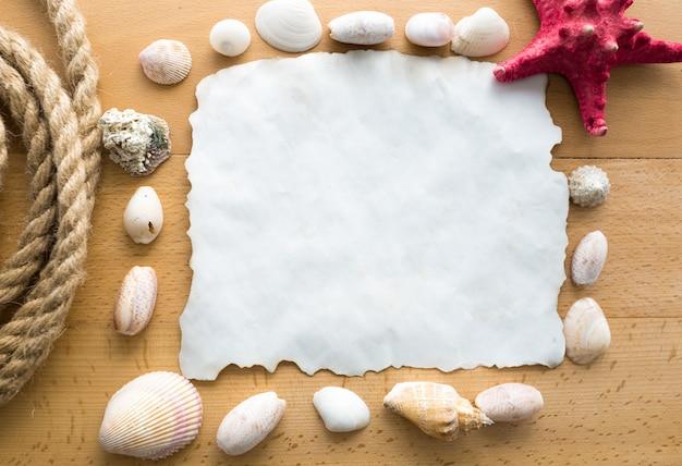 Velho pedaço de papel em branco com conchas, corda e estrelas do mar