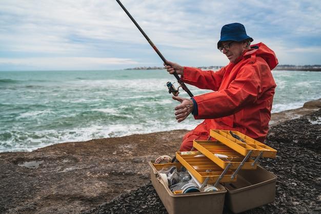 Velho pesca no mar.