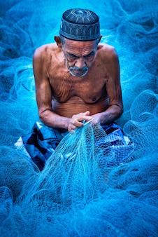 Velho pescador costurando redes de pesca azuis sentado no chão