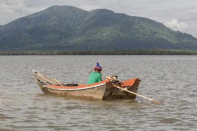 Velho pescador no velho barco de madeira.