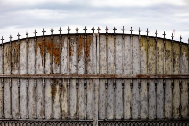 Velho portão enferrujado em uma casa abandonada. portão quebrado.