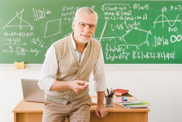 Velho professor sorridente com giz em sala de aula