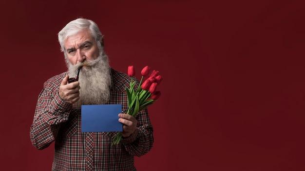 Velho, segurando flores