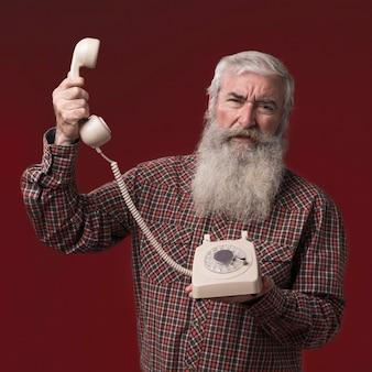 Velho, segurando um telefone