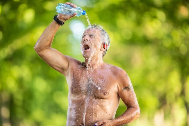 Velho sem camisa derrama água de uma garrafa na cabeça e no rosto ao ar livre em um dia quente de verão.