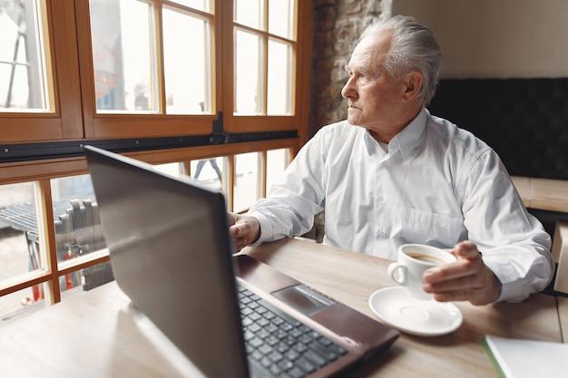 Velho sentado à mesa e trabalhando com um laptop
