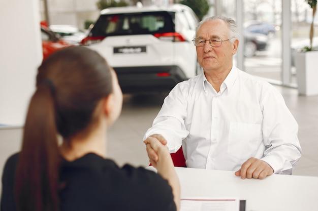 Velho sentado em um salão de carro e conversando com o gerente