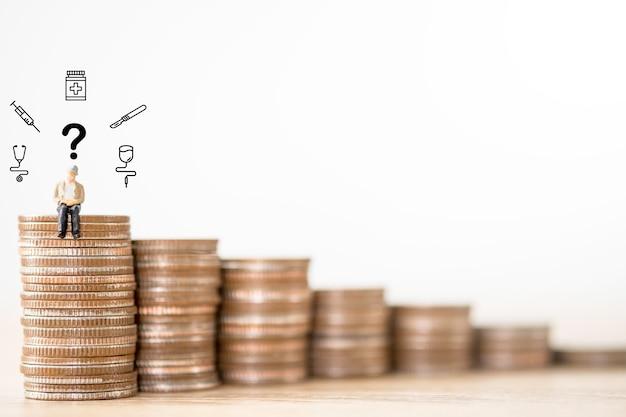 Velho sentado nas moedas de empilhamento com pergunta e item médico. conceito de seleção de negócios de seguro de saúde.