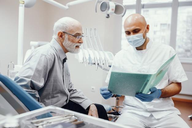Velho sentado no consultório do dentista