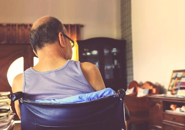 Velho sentado sozinho em uma cadeira de rodas em casa