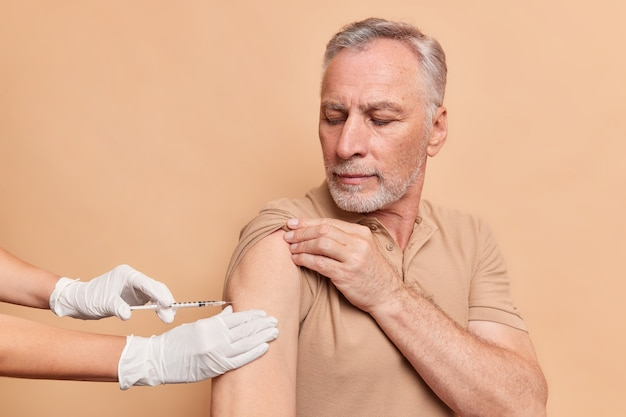Velho sério de cabelos grisalhos recebendo injeção de vacina contra coronavírus usa camiseta isolada na parede bege do estúdio
