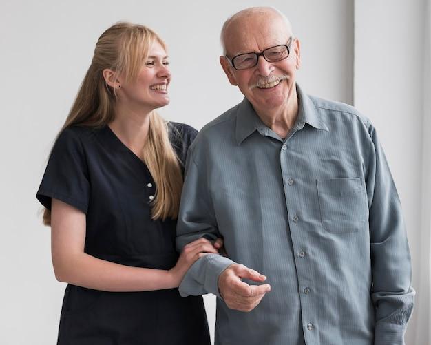 Velho sorridente e enfermeira