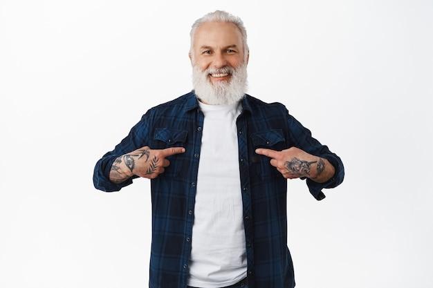 Velho sorridente e estiloso com tatuagens e barba, apontando para si mesmo, me escolhe, quer ser voluntário, indicá-lo, se gabar ou se autopromover, em pé sobre uma parede branca