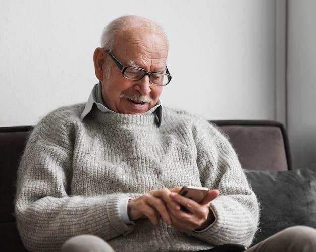 Velho sorridente usando smartphone em uma casa de repouso