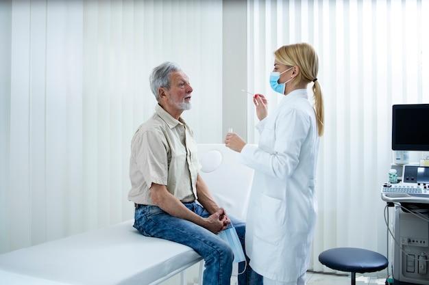 Velho tirando um cotonete do nariz ou da garganta para fazer o teste do vírus corona.