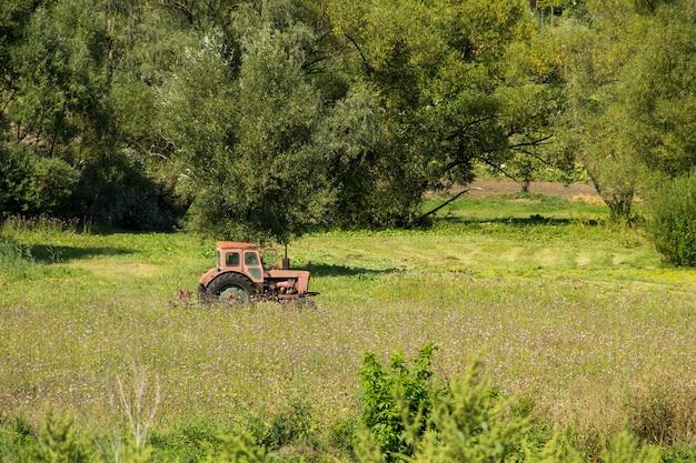 Velho trator vermelho feno em um prado