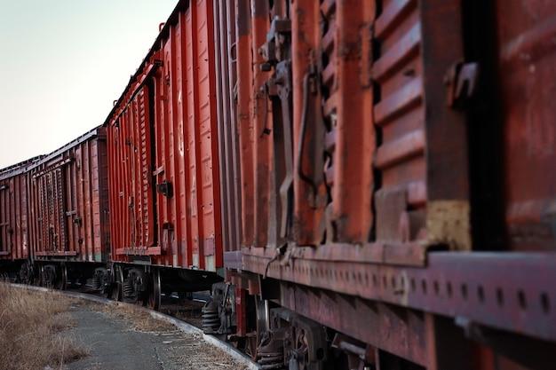 Velho trem de carga enferrujado fica sobre trilhos, primeiro plano, nitidez borrada do meio do vagão até o final do trem