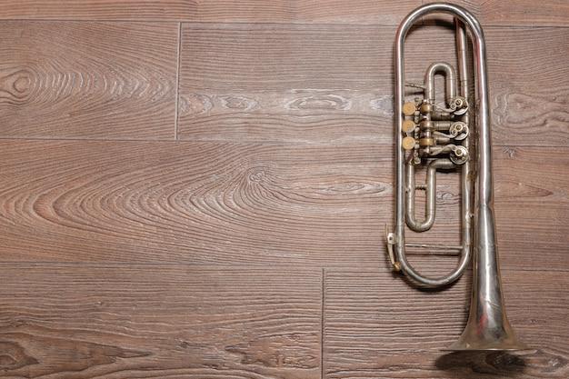 Velho trompete enferrujado pousado no chão de madeira