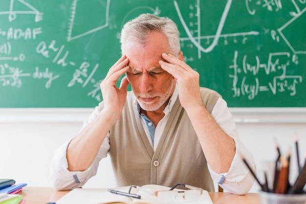 Velho tutor com dor de cabeça na sala de aula