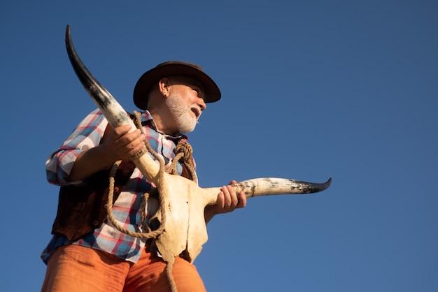 Velho vaqueiro do oeste selvagem segurando o crânio da vaca. homem ocidental sênior com barba e jaqueta marrom, chapéu. esqueleto de osso de búfalo.