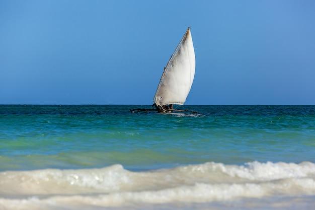 Velho veleiro de madeira africano desliza sobre as ondas do oceano índico,