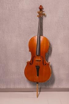 Velho violoncelo maltratado em pé perto de uma parede texturizada cinza.