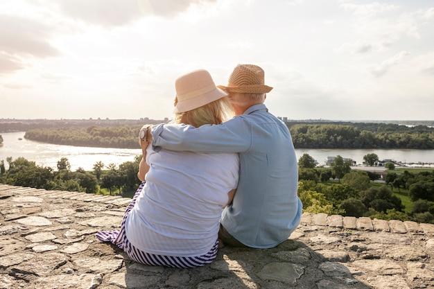 Velhos amantes sentado backview tiro Foto Premium