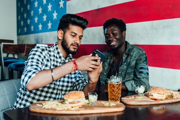 Velhos amigos alegres se divertindo com o smartphone e bebendo chope com hambúrgueres no balcão do bar no pub.