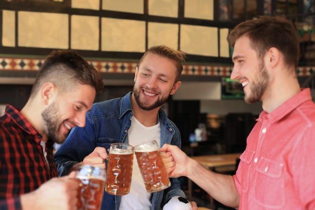 Velhos amigos alegres se divertindo e bebendo cerveja no balcão do bar no pub.