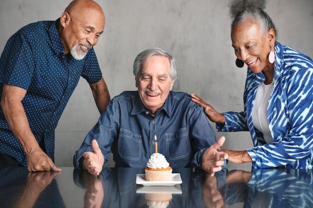 Velhos amigos comemorando aniversário com bolo