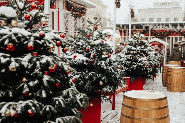 Velhos barris de madeira vintage e árvores de natal festivas no mercado de natal