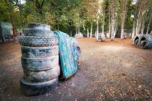 Velhos barris enferrujados e pneus danificados na base de paintball onde os jogadores empolgados estão escondidos