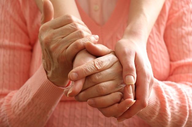 Velhos e jovens de mãos dadas, closeup